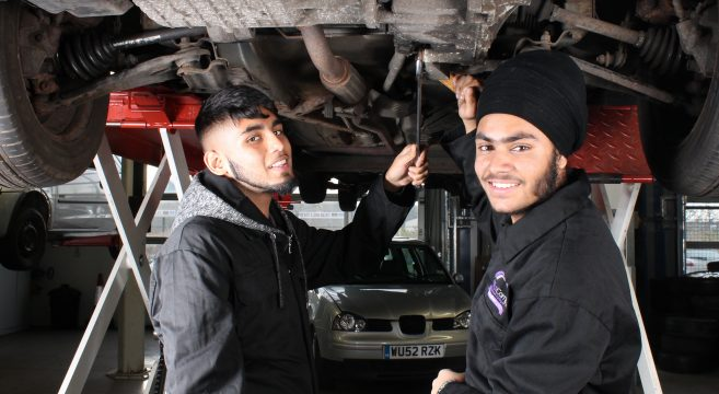 Two male automotive students pictured working underneath a car