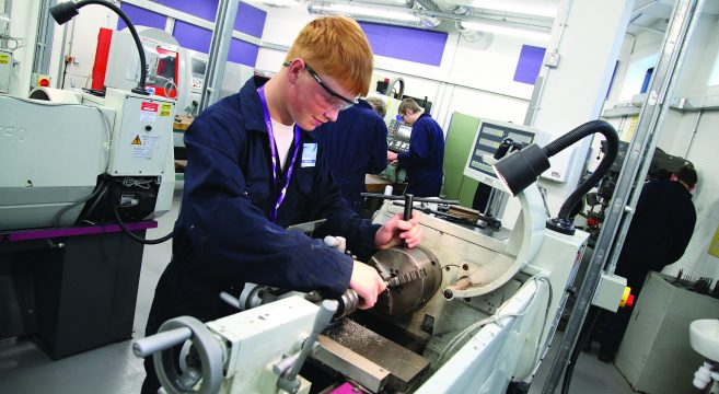 Engineering student working on a CNC lathe