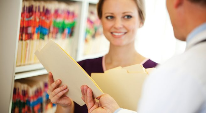 Female healthcare worker being given a folder by a colleague