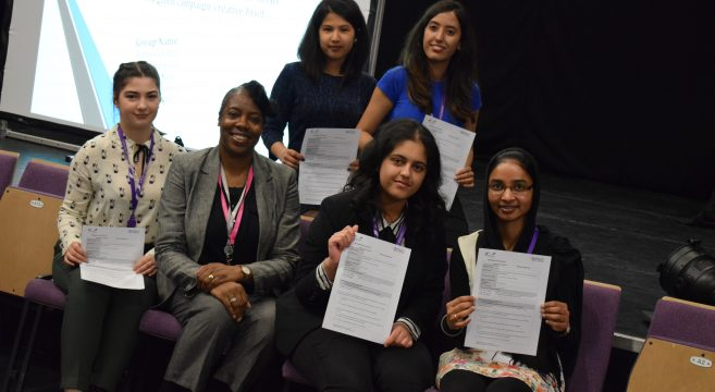 Group of female students showing their BTEC certificates pictured next to female teacher