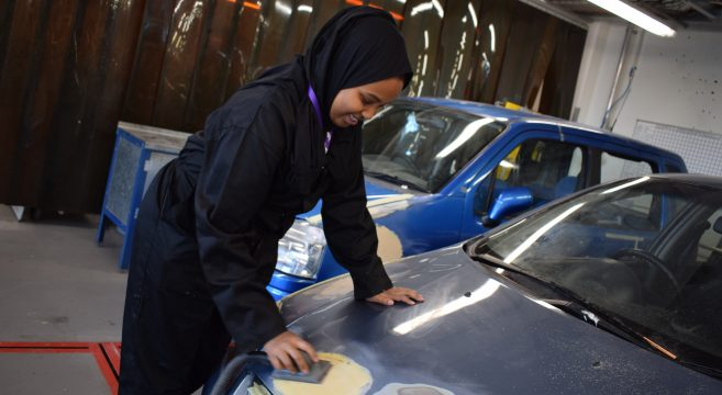 Female automotive student repairing a car