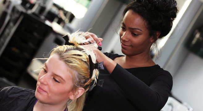 Black female Hairdressing student putting blonde client's hair in clips