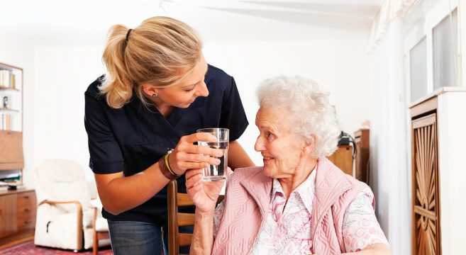 Female care worker offering female patient a glass of water