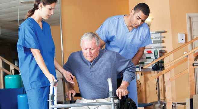 Female and male healthcare workers caring for man in wheelchair