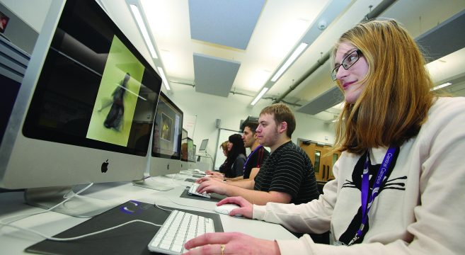Media students editing images on computers in graphics suite