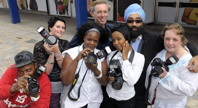 Group of student photographers with lecturer holding cameras at shopping centre
