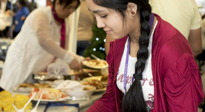 ESOL female student selecting food from a buffet