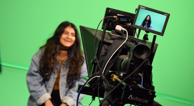 Female student sat in front of a green screen being filmed by TV camera