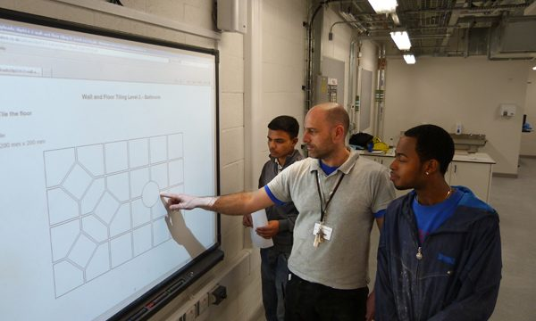 Tiling lecturer showing two male students a design on a smartboard screen