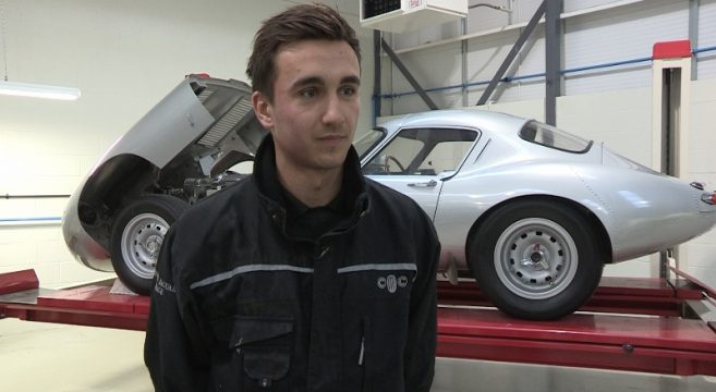 Tom Smallman Automotive Apprentice in front of a car