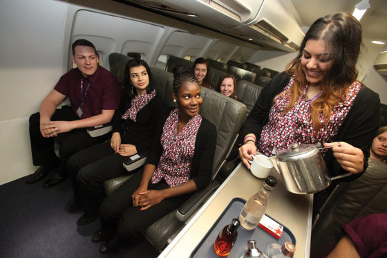 Travel student serving drinks in aircraft cabin