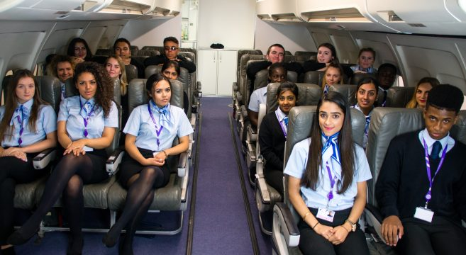 Group photo of Travel, Aviation & Hospitality students inside a model aircraft