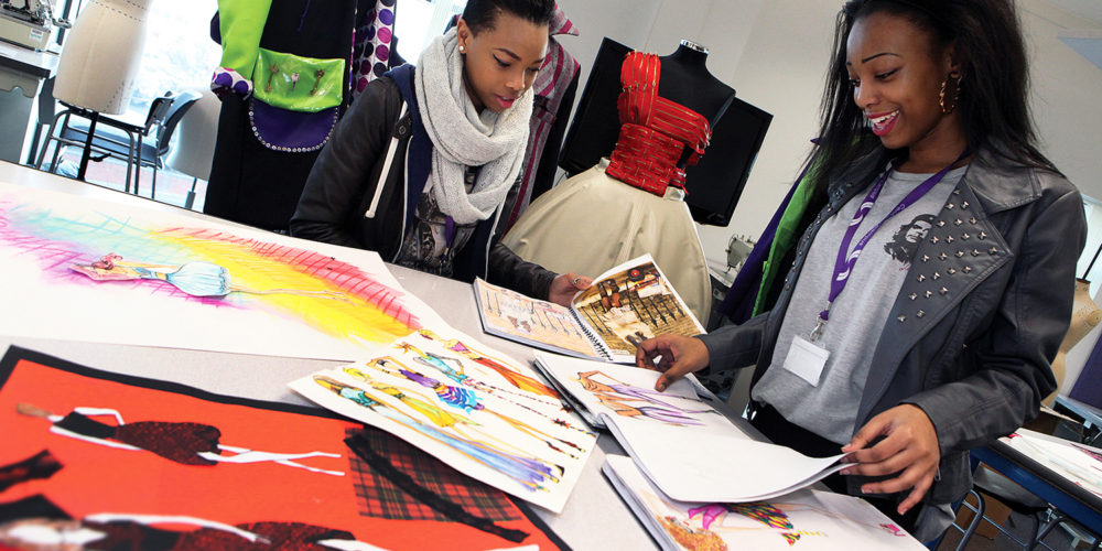 Smiling fashion students looking at design sketchbooks in the studio