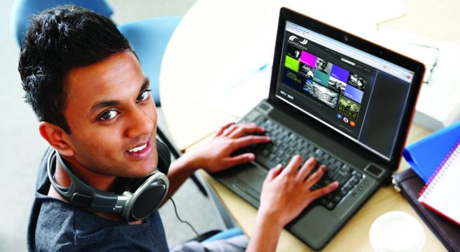 Male student looking at college website on laptop