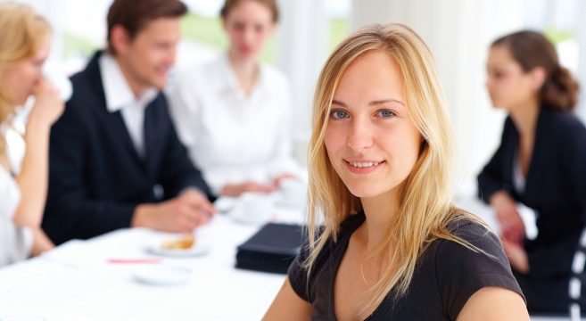 White blonde businesswoman with colleagues' meeting in background