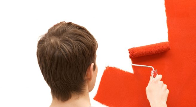 Student painting white wall red with roller