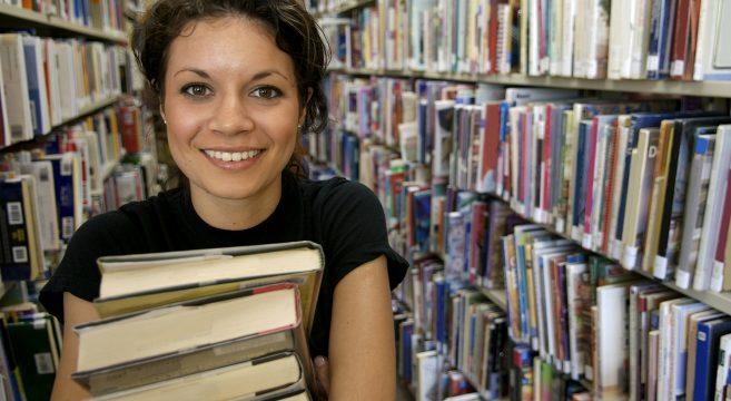 Student carrying a pile of books in library