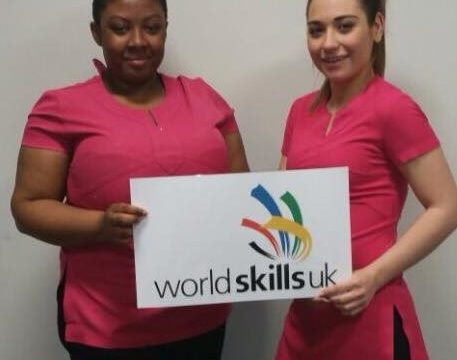 Two female beauty students in pink uniform with World Skills sign
