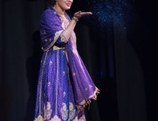 Hair show model in purple sari blowing glitter