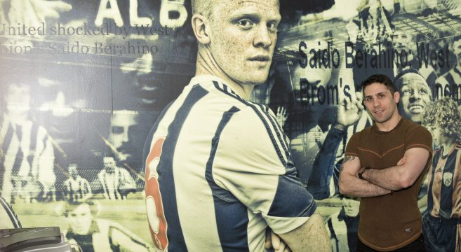 Photography student stands in front of his mural created for WBA Academy