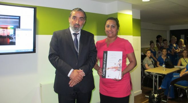 Beauty student presented with certificate by college manager
