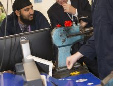 Chair of Governors John Tew watches a laser cutting demo by engineering students