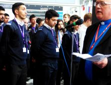 Vicar talking into microphone watched by Public Services students