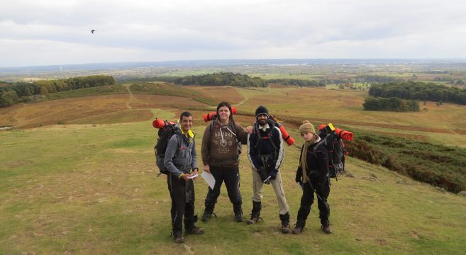 Four students standing on a hill wearing expedition gear