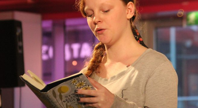 Student reading poetry out from a book