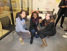 Three female students kneeling