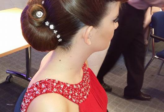 Female student in red dress modelling a hair up style