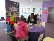 Lecturer standing and showing people careers literature at table