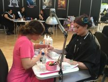 Nail art competitor and model at table