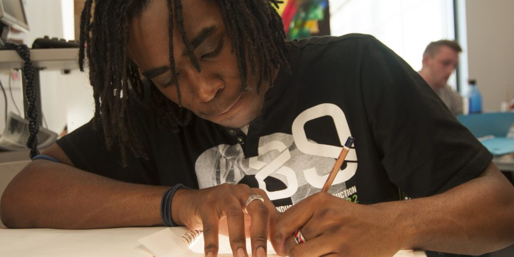 Male art student drawing on a piece of paper
