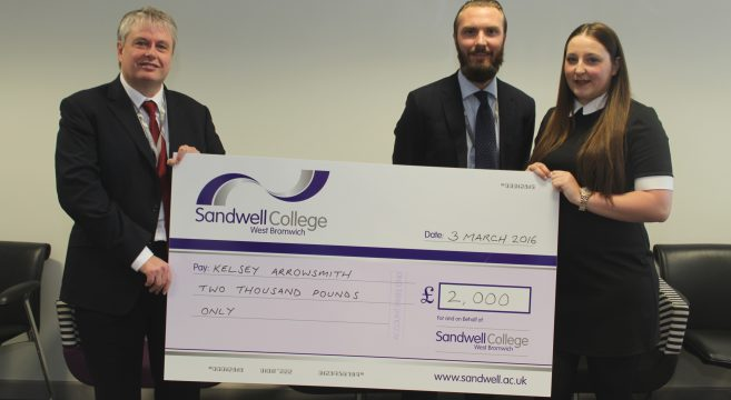 Two male staff and female student holding giant cheque