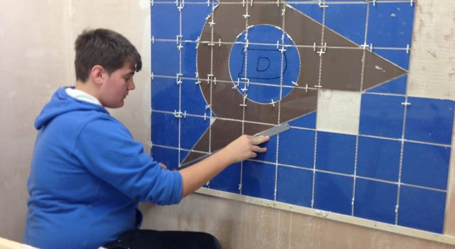 Male student measuring blue and grey tiles