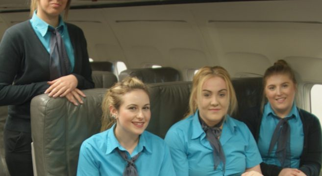 Four female travel students in aircraft cabin