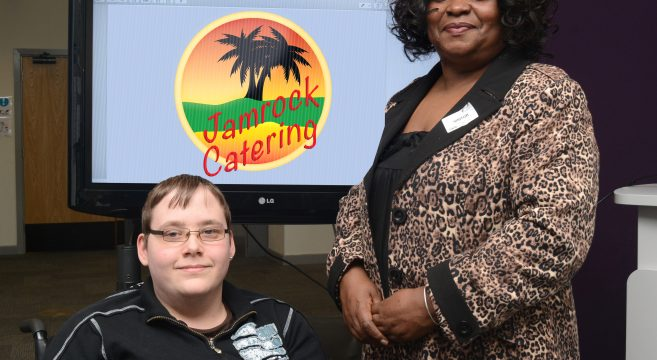Male student in wheelchair with woman standing in front of Jamrock Catering logo on screen
