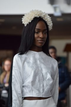 Fashion show model wearing white top and hairband