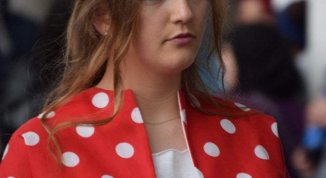 Fashion show model wearing red and white polka dot jacket