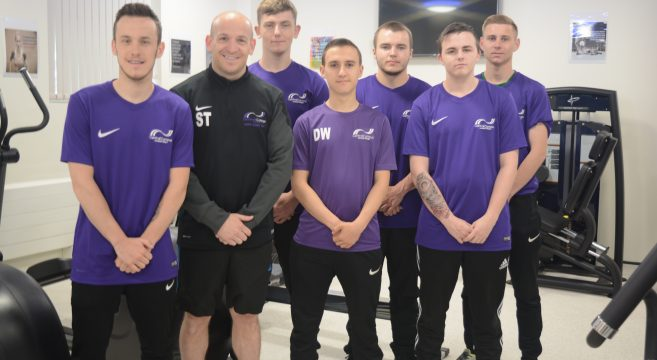 Sport lecturer with six male students in gym