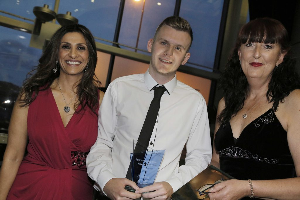 Customer service student receiving award from two presenters