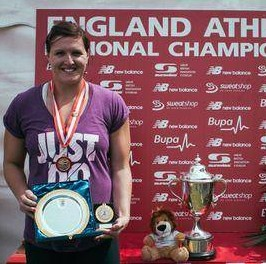 Female athlete wearing medal and holding plate