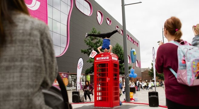 Acrobat standing on head on top of red phone box