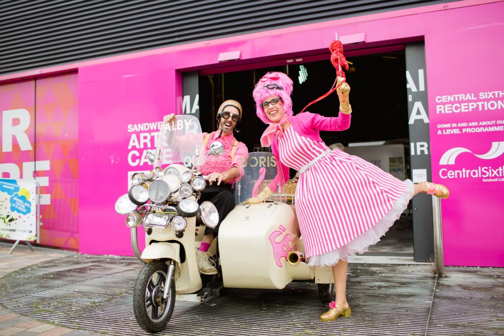 Motorbike and sidecar with couple dressed in pink