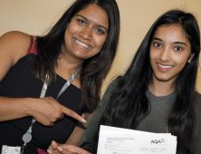 Female student showing her results pictured with staff member