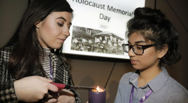 Female student lighting candle at Holocaust Memorial