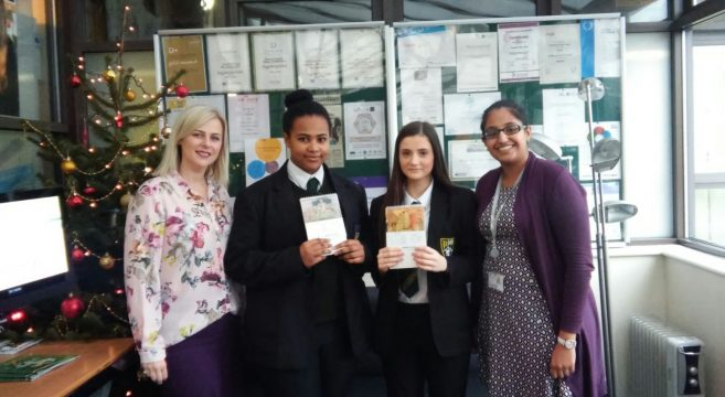 Two female secondary school students showing their calendar design that won an award pictured with staff members