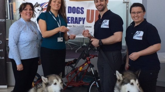 Sandwell College staff members giving cheque to representatives of Sled Dogs charity