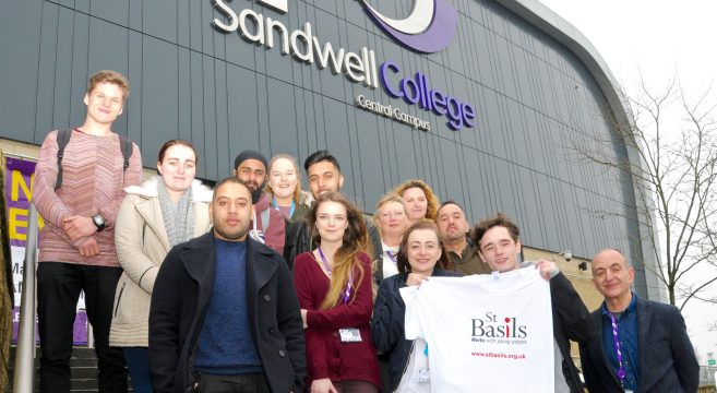 A group of students pictured outside Sandwell College campus, male student holding white St Basils t-shirt